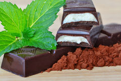 Dark chocolate sticks with mint fondant filling. And cacao on wooden table royalty free stock photo