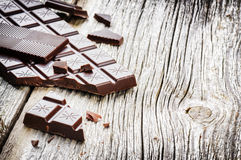 Dark chocolate tablets on old wood background Royalty Free Stock Photos