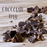 Dark chocolate and text chocolate day. The text chocolate day and some pieces of dark chocolate on a rustic wooden surface Royalty Free Stock Photo