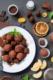 Dark chocolate truffle with orange peel. Dark chocolate truffles with orange peel on white plate over dark stone background. Top view Royalty Free Stock Photos