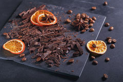 Dark chopping chocolate, black roasted coffee beans, dried lemon. Slices with spices anise on slate board over black textural background. Chocolate dessert Royalty Free Stock Photography