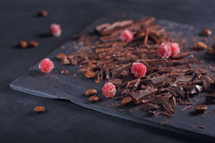 Dark chopping chocolate, black roasted coffee beans, red berries royalty free stock image