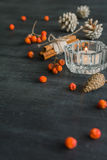 Dark Christmas background with candles and berries of mountain ash. White pine cones. Branches acorns. Royalty Free Stock Photo