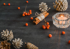 Dark Christmas background with candles and berries of mountain ash. White pine cones. Branches acorns. Stock Photo
