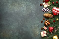 Dark christmas background with fir branchs,toys and gift boxes . Dark christmas background with fir branchs,toys and gift boxes on a green slate,stone or Stock Photography