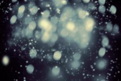 Dark Christmas background with snowflakes and glittering boke. H stars. Night Abstract Glowing blurred lights stock photography