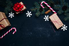 Dark christmas background with xmas decoration gift box balls to. Ys and christmas candy cane festive concept top view Stock Photos