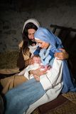 Dark christmas nativity scene. Live Christmas nativity scene in an old barn - Reenactment play with authentic costumes. The baby is a property released doll stock photo