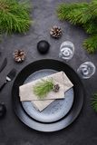 Dark christmas table setting design. Black plates, champagne glasses, fork and knife set with napkin, fir branch. Christmas decorations royalty free stock photography