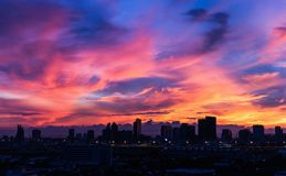 Dark city covered by colorful morning sky. Dark city covered by dramatic colorful morning sky with moving clouds before sunrise after storm at night Royalty Free Stock Photography