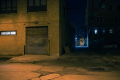 Dark city street corner and alley at night. Dark city street corner and alley with an industrial building entrance at night Royalty Free Stock Images