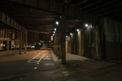Dark City Train Tunnel Street at Night. Dark urban downtown city elevated train tunnel and street at night Stock Photo