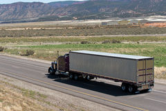 Dark Classic semi truck and trailer on the road with nature view Stock Photo