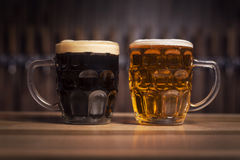Dark and cleer beers in a large beer mug stands on the bar. Dark beer in a large beer mug stands on the bar against the background of the taps Stock Photo