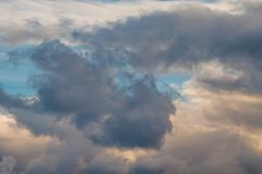 Dark Cloud Formation. A tuft of dark clouds surrounded by white fluffy clouds agains a blue sky and yellow morning sunlight stock photography