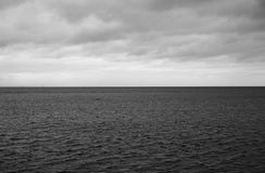 Dark cloud over sea. Dark cloud over the Gulf of Finland of Baltic Sea, Russia. Black and white stock photos