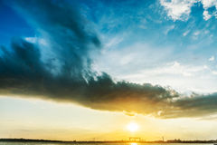 Dark cloud in sunset over sun Royalty Free Stock Image
