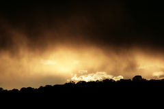 Dark Clouds. A dark storm rolls in over a bright sunset royalty free stock photo
