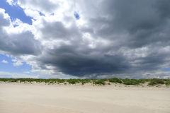 Dark clouds above dunes. Cornwall England Stock Image
