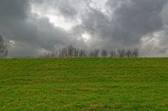 Dark clouds above green meadow. In Autumn, near  Hamburg, Germany Stock Image