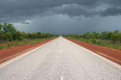 Dark clouds above the road. Australian road with red dirt and shrubby landscape and dark clouds on the sky. Australia Royalty Free Stock Photo