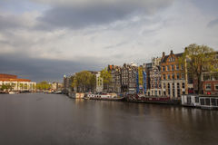 Dark clouds above traditional houses in Amsterdam Stock Photos