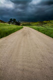 Dark clouds ahead. Road that leads into possible danger with dark clouds looming stock image