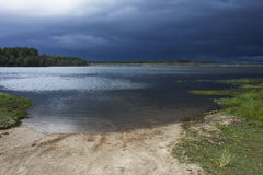 Dark clouds approaching a lake. Royalty Free Stock Photography