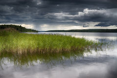 Dramatic sky over lake. Dark clouds and dramatic sky over lake Royalty Free Stock Photos