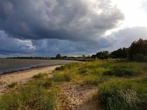 Dark clouds filled with rain meet the sunshine that lights up the sandy beach in Halmstad, Sweden. The sun still lights up the sandy beach making all colours so Royalty Free Stock Photo