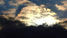 Dark clouds are floating in the evening sky. The clouds are illuminated by the setting sun stock video footage