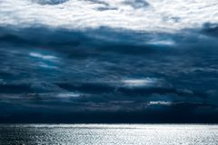 Dark clouds forming above the calm waves of the Atlantic Ocean, Block Island, RI royalty free stock image