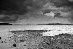 Dark clouds gathering over beach. Dark storm clouds gathering over beach, in black and white Stock Images