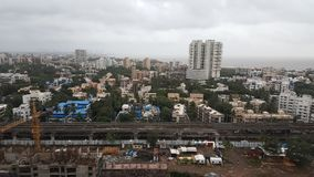Dark clouds hover over the Landscape of Mumbai Suburb on a rainy day. Mumbai Metro between High rise buildings along the sea coast in the western suburbs Versova stock photography