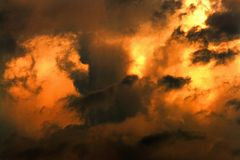 Dark clouds illuminated by the bright light of the sun. Apocalyptic dramatic background royalty free stock photo