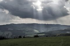 Dark clouds let sunlight into the green meadow Royalty Free Stock Photo
