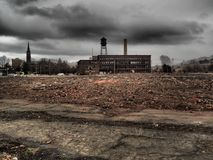 Urban decay with vacant factory. Dark clouds and ominous sky create mood with vacant lot and vacant factory in the background Royalty Free Stock Image