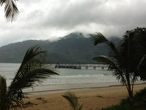 Dark clouds over a beautiful tropical beach with palm trees on Tioman island in Malaysia. Clouds over a tropical beach with palm trees on Tioman island in Stock Photo