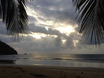 Dark clouds over a beautiful tropical beach with palm trees on Tioman island in Malaysia. Clouds over a tropical beach with palm trees on Tioman island in Royalty Free Stock Photos