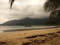 Dark clouds over a beautiful tropical beach with palm trees on Tioman island in Malaysia. Clouds over a tropical beach with palm trees on Tioman island in Royalty Free Stock Image
