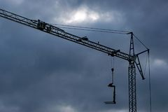 Dark clouds over a construction crane stock image