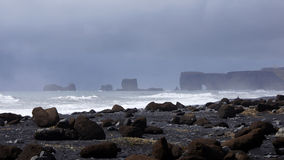 Dark clouds over Dyrholaey in Vik. Dark clouds over Dyrholaey from Reynisdrangar beach in Vik in Iceland stock photo