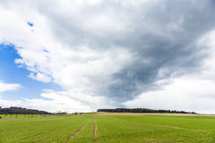 Dark clouds over fields in spring Royalty Free Stock Images