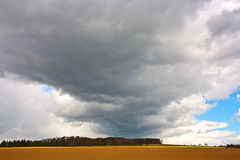 Dark clouds over fields in spring Royalty Free Stock Photo