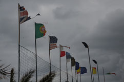 Dark clouds over the flags of different countries. Royalty Free Stock Images