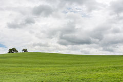 Dark clouds over a grass hill (left). Dark clouds over a grass hill royalty free stock image