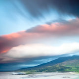 Dark clouds over Irish coast Dingle peninsula. Dark clouds during sunset over Irish coast Dingle peninsula Kerry district hills and beach long exposure image Stock Photo