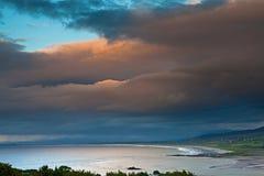 Dark clouds over Irish coast Dingle peninsula. Dark clouds during sunset over Irish coast Dingle peninsula Kerry district hills and beach long exposure image royalty free stock image