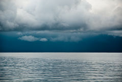 Dark clouds over lake. Landscape view to the horizon of dark clouds in the sky over a lake royalty free stock photos