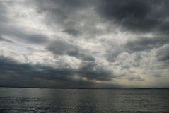 Dark clouds over a lake. Dark cloudy sky over a lake royalty free stock photography